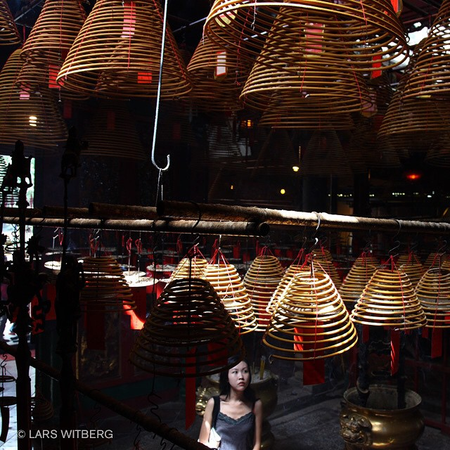 Young woman write her prayers inside a coil of incense and hangs it high to attract the attention of the gods. Man Mo temple in Hong Kong.  #temple #travel #hongkong #china #Travler_stories #photo #picoftheday